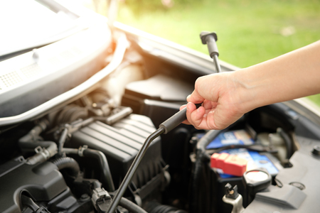 The car is opening the hood to check the engine oil.