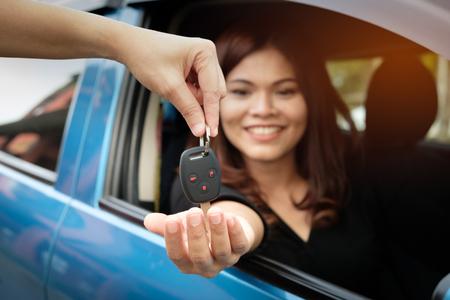 アジアの女性は、売り手の手から車のキーを取得します。 写真素材