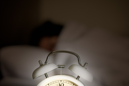 A glowing alarm clock is placed in front of a sleeping woman.