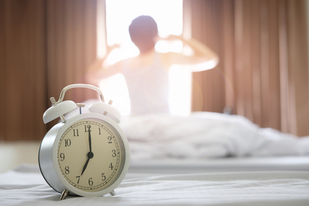 The alarm clocks in the morning, causing the woman to wake up and twist her body. Stock Photo