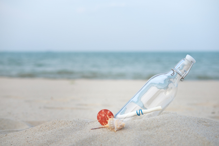 castaway: Bottle with a message on the desert beach by the sea with copy space to write. Stock Photo