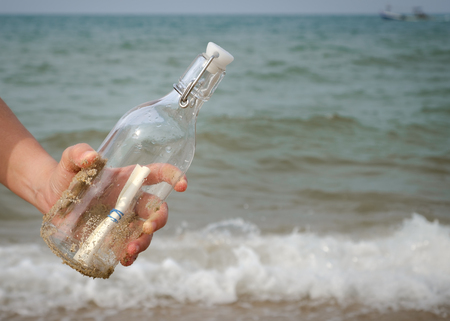 Hand holding a bottle with a letter inserted inside by the sea. Stock Photo
