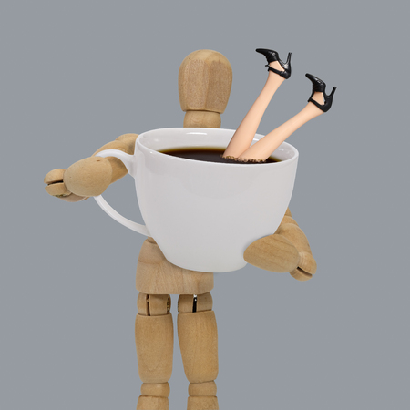 Wooden dummy holding a oversized cup of black coffee with legs of woman isolated on blue background.