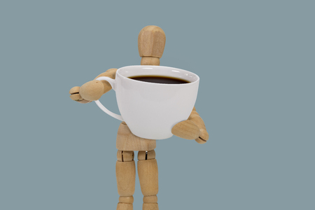 Wooden dummy holding a oversized cup of black coffee  on blue background Stock Photo