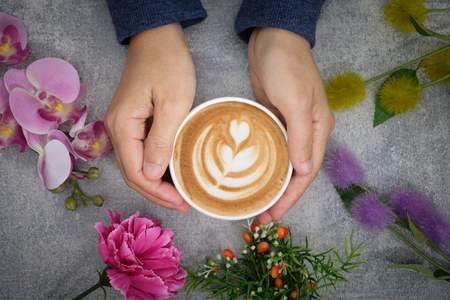table top: The hands in the sweater are holding a cup of coffee and there are many colored flowers surrounded.