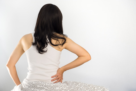 Woman sitting back in bed with back pain and take the handle of the lumbar.
