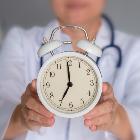 Doctor is holding alarm clock to show punctuality. Time concept.