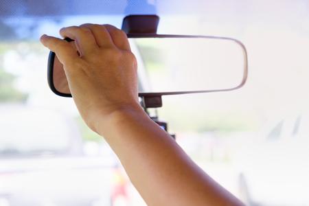 手は良いブレーキと安全な車のためにバックミラーを調整しています 写真素材