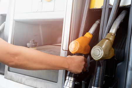The gold car is filling the fuel at the oil station. Hand holding Fuel nozzle in gas pump.
