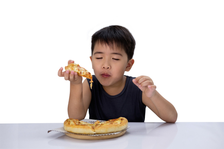 Cute boy is closing his eyes and enjoying eating pizza isolated on white background. Pizzeria can be used as an illustration food menu.