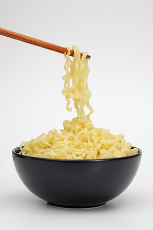 Black bowl of instant noodles with chopsticks isolated on white background.