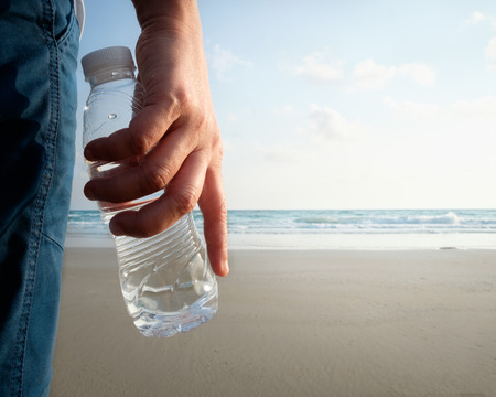 Bottle of drinking water in womans hand by the sea.