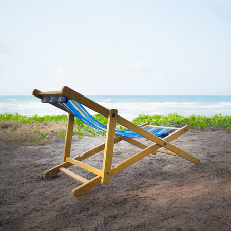 An yellow beach chair rests on the white sand of the beach and Bright blue sea with white clouds, at Rayong Thailand.