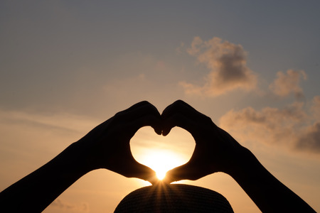 silhouette Hands are making a heart shape to let the sun pass through.