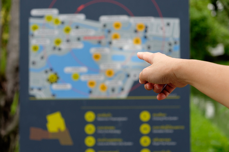 Hand pointing to a map in the garden to go to desired destinations. Stock Photo