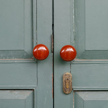 Antique red Doors locked on green door.