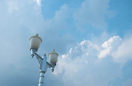 Decorated street lamp on the background of blue sky with white clouds. Copy space.