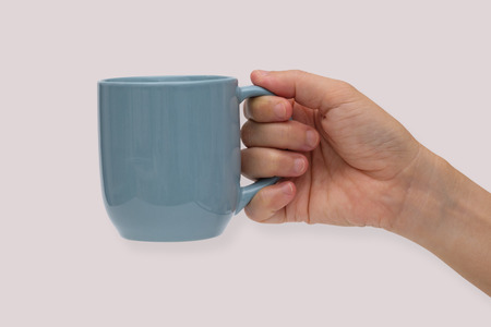 Hand holding blue ceramic mug or Coffee cup with shadow isolated on pink background.