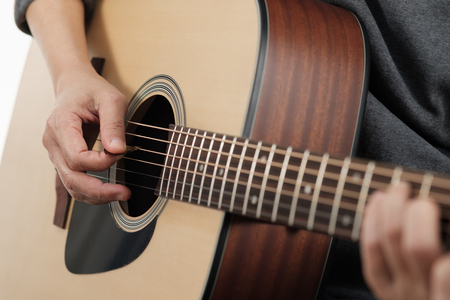 Close up womans hands playing acoustic guitar.
