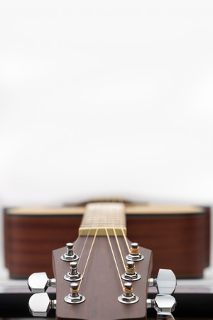 Close up of an acoustic guitar headstock on white background with copy space.