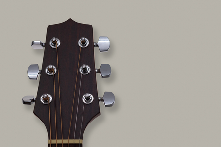 Close up of an acoustic guitar headstock on grey background. Stock Photo