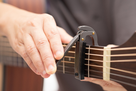Close up-The hands are adjusting the capo to adjust the sound of the guitar.