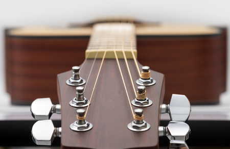 Close up of an acoustic guitar headstock on white background.
