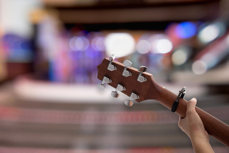 Close up womans hands playing acoustic guitar on bokeh background. Stock Photo