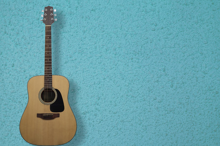 Guitar is a classic instrument on blue cement background with copy space. Stock Photo