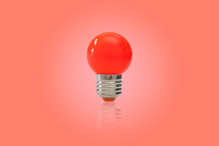 Red light bulb isolated on red background. Stock Photo