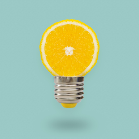 Yellow Lemon light bulb on bright blue background. Summer fun concept. Stock Photo