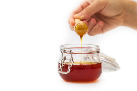 Hand holding a honey dripper on white background. Food concept.