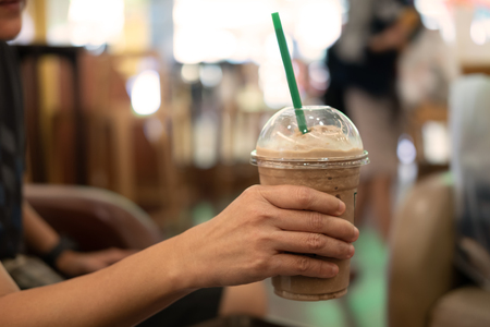 Woman holding plastic glass of iced coffee with milk, image for beverage.