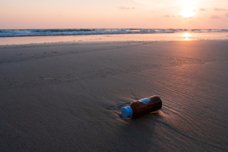 Glass bottles is dump into the sea, dirty waste on beach in summer day. Stock Photo