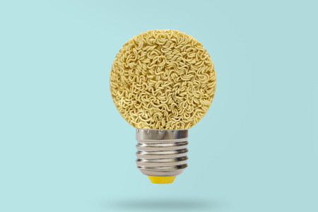 Idea picture-Nests of dried noodles with lamp on blue background. Stock Photo