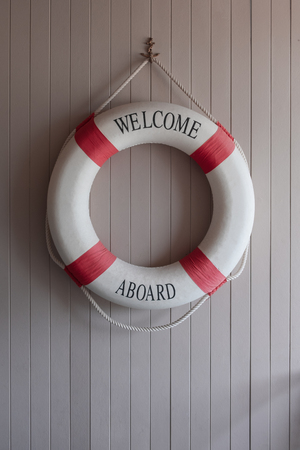 Red-white lifebuoy, safety torus on wooden board.