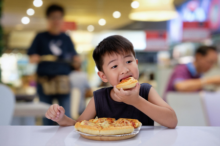 Asian 6-7 year boy is happy to eating pizza with a hot cheese melt stretched on a wooden pad in resturant.