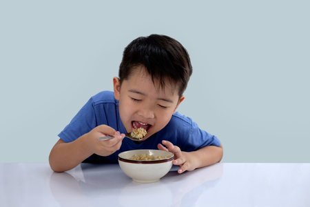 the Asian boy is eating delicious rice and has a very happy face. Stock Photo