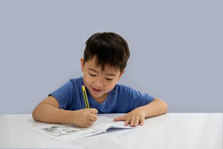 Asian boys are doing some writing on the book isolated on blue background.