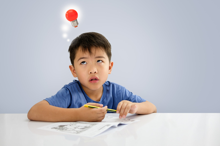 The boy is looking up,  While sitting on some writing on the notebook. Stock Photo