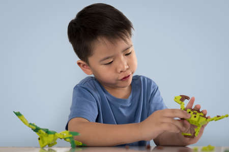 Portrait of cute asian boy playing with colorful plastic toy bricks at the table. Stock Photo
