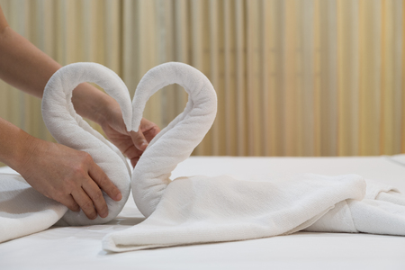 Close-up of hands putting folded swans bird of fresh white bath towels on the bed sheet in the hotel.