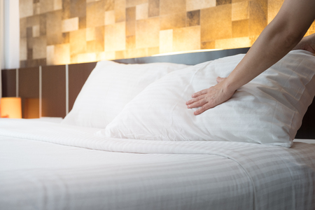 Hotel room service hands set up white pillow on the bed in the hotel. Stock Photo