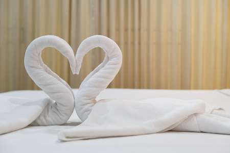 Close-up folded swans bird of fresh white bath towels on the bed sheet in the hotel. Stock Photo