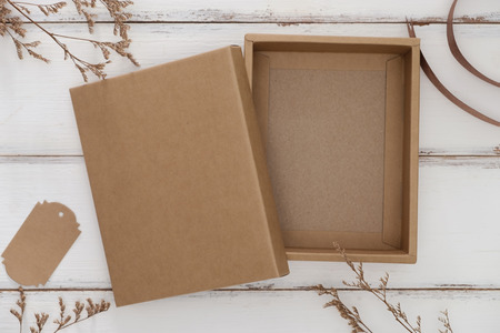 Opened cardboard box on white wooden background with dry grass.