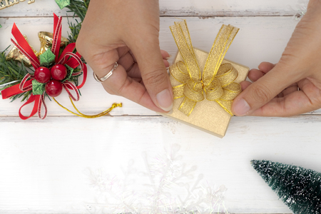 Top view of female hands tying a golden bow on a gift box. Stock Photo