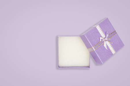 Top view of opened purple gift box on purple background. with copy space for text.