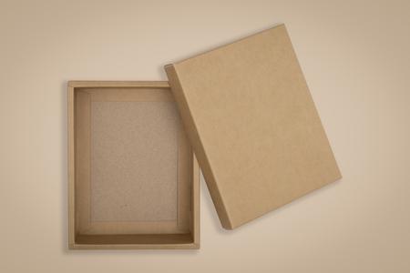 Scatola di cartone aperta su uno sfondo marrone.