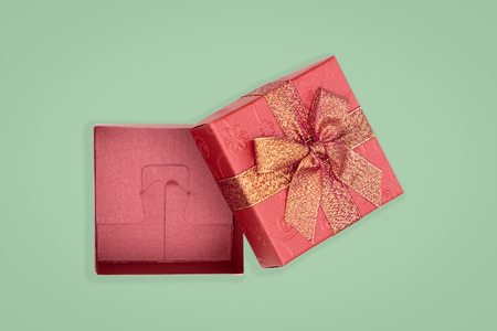 Top view of opened red gift box on green background. with copy space for text.