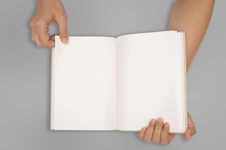 Top view- two hands hold a empty book spread.